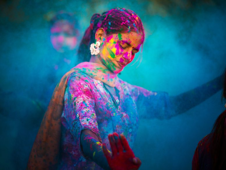 Young woman dancing around blue powder while celebrating the Indian Holi Day